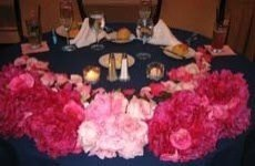 Bouquets of flowers placed around the edge of the bride and groom table