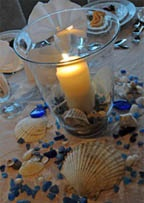 cheap idea of having a candle in a vase with sea shells and stones