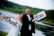 Bride and groom holding a big sign that says thank you
