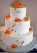 Picture of a fall wedding cake with orange flowers and green swirling.