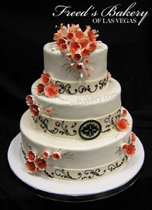 Beautiful fall wedding cake with orange flowers and black scrolling