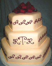 Three tier white cake with red fondant bow and couples initials