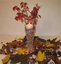 Autumn leaves for your reception centerpiece including a candle with flowers