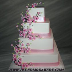 Unusual wedding cakes with pink, pearlized bands and cherry blossoms and branches