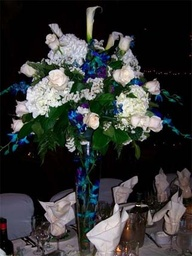 Tall centerpiece in crystal vase with flowers