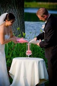 Bride and groom pouring sand into vase