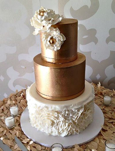 Elegant Wedding Cake with gold petals on the cake table.