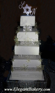 Square and elegantly tiered wedding cake is separated with pillars and has a large silver snowflake topper