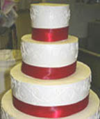 Beautiful white wedding cake with red ribbon between each layer - perfect for a Christmas theme
