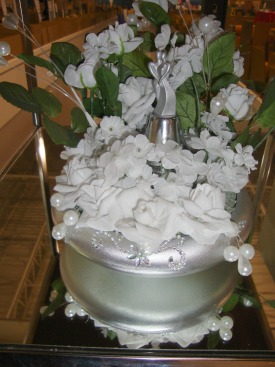 Photo of a Winter Wedding Centerpiece with a bridal couple in the center of the white flowers