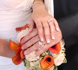 cheap wedding ideas bride and grooms hands on flower bouquet