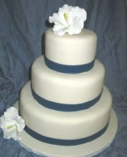 Simple and elegant three tier weding cake with blue ribbon separating each  layer wit a lovely flower topper