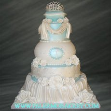 Picture of an elegant white cake with draping and a crystal tiarra.
