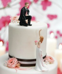 Bride waving to her groom while he sits on top of their cake
